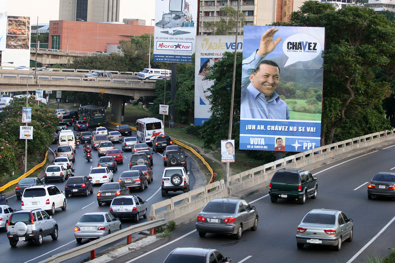 Traffic passes near a banner for Venezuelan President Hugo Chavez in Caracas, Venezuela, Nov. 30, 2006. Chavez, first elected President in 1998 leads some opinion polls for the Dec. 3 2006 election with up to 60 percent of voter intentions. Chavez is a master of marketing and has achieved pop star status among the lower classes, who adore him.(AustralFoto/Douglas Engle)