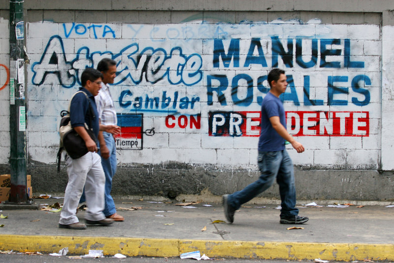 Pedestrians walk past a campaign advertisement of presidential candidate Manuel Rosales in Caracas, Venezuela, Dec. 12, 2006. Rosales, who receives massive support form the middle and upper classes, is still not able to compete with the pop star image of Venezuelan President Hugo Chavez. Chavez leads some opinion polls for the Dec. 3 2006 election with up to 60 percent of voter intentions.(AustralFoto/Douglas Engle)