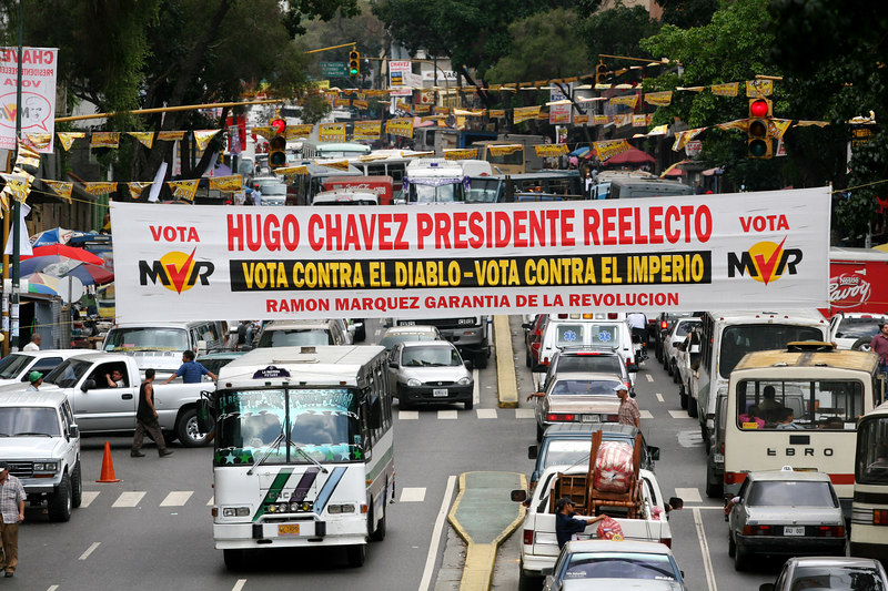 """Traffic passes below a campaign banner for Venezuelan President Hugo Chavez in Caracas, Venezuela, Nov. 30, 2006 which reads """"Vote against the Devil, vote against the empire."""" Chavez, first elected President in 1998 leads some opinion polls for the Dec. 3 2006 election with up to 60 percent of voter intentions. Chavez is a master of marketing and has achieved pop star status among the lower classes, who adore him.(AustralFoto/Douglas Engle)"""
