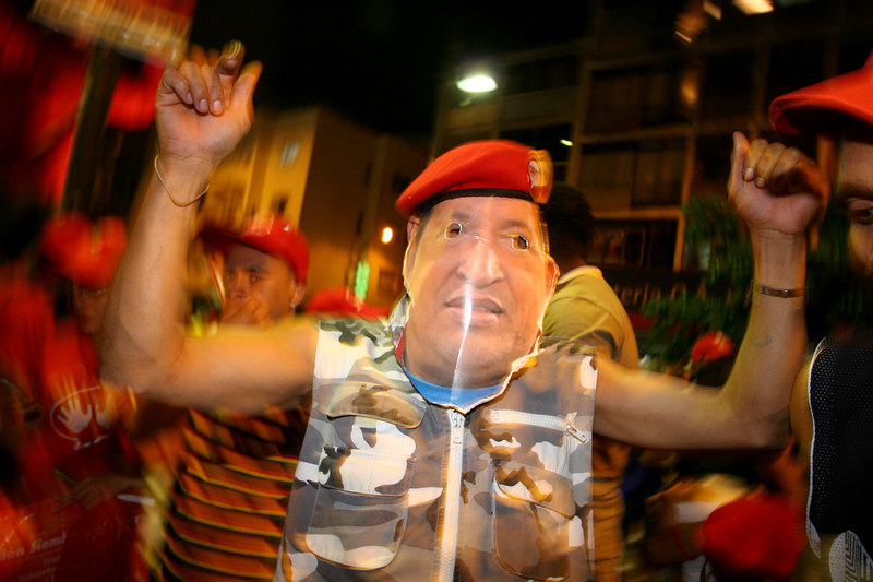 A supporter of Venezuelan President Hugo Chavez wears a Chavez mask during a rally in Caracas, Venezuela, Nov. 30, 2006. Chavez, first elected President in 1998 leads some opinion polls for the Dec. 3 2006 election with up to 60 percent of voter intentions. Chavez is a master of marketing and has achieved pop star status among the lower classes, who adore him.(AustralFoto/Douglas Engle)