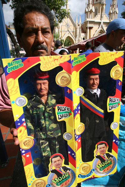 """A man offers dolls of Venezuelan President Hugo Chavez, called """"Chavito"""" in Caracas, Venezuela, Nov. 30, 2006. Chavez, first elected President in 1998 leads some opinion polls for the Dec. 3 2006 election with up to 60 percent of voter intentions. Chavez is a master of marketing and has achieved pop star status among the lower classes, who adore him.(AustralFoto/Douglas Engle)"""