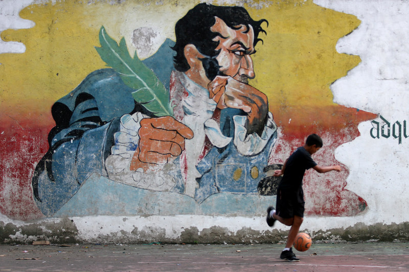 A boy plays near a mural of Simon Bolivar in the 23 de enero neighborhood in Caracas, Venezuela, Nov. 29, 2006. The poor working class neighborhood is a stronghold of support for Venezuelan President Hugo Chavez. First elected President in 1998, Chavez leads some opinion polls for the Dec. 3 2006 election with up to 60 percent of voter intentions. Chavez is a master of marketing and has achieved pop star status among the lower classes, who adore him.(AustralFoto/Douglas Engle)
