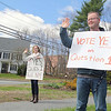 Susan and Justin Whittemore Hold vote yes signs in support of the school vote as they wave to cars that where going around the rotary in Pepperell on Monday.   SENTINEL & ENTERPRISE/JOHN LOVE