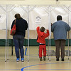 Dylan Peterson, 5, checks things out as his aunt Christina Morneau, on left, and his grandmother Judy St. Thomas fill out their ballots in Ashburnham on Tuesday. SENTINEL& ENTERPRISE/JOHN LOVE