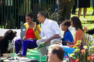 "Barack and Michelle Obama join daughters Sasha and Malia in reading books to kids. In photo, President Obama reads from Maurice Sendak's ""Where the Wild Things Are."" First dog Bo looks on. The 134th annual White House Egg Roll attracted over 30,000 visitors to the White House South Lawn for a day of racing, reading and fun on Monday, April 9, 2012. The theme of this year's egg roll was ""Let's Go, Let's Play, Let's Move!"" which was modeled after the First Lady's ""Let's Move!"" campaign.  (Photo by Jeff Malet)"