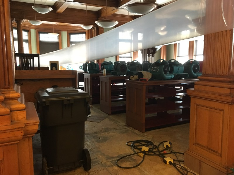 Turbo drier fans whirred on the first floor of the Pollard Memorial Library Thursday, part of the drying process after 5,000 gallons of water were dumped through each floor of the building due to a burst pipe over the weekend. SUN / ALANA MELANSON