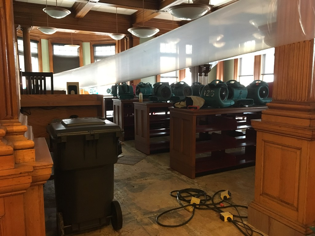 . Turbo drier fans whirred on the first floor of the Pollard Memorial Library Thursday, part of the drying process after 5,000 gallons of water were dumped through each floor of the building due to a burst pipe over the weekend. SUN / ALANA MELANSON