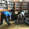 ServiceMaster employees Jacob Scott, of Concord, N.H., and Jenn Clarke, of Nashua, remove damaged carpeting from the first floor of the Pollard Memorial Library Thursday.  SUN / ALANA MELANSON