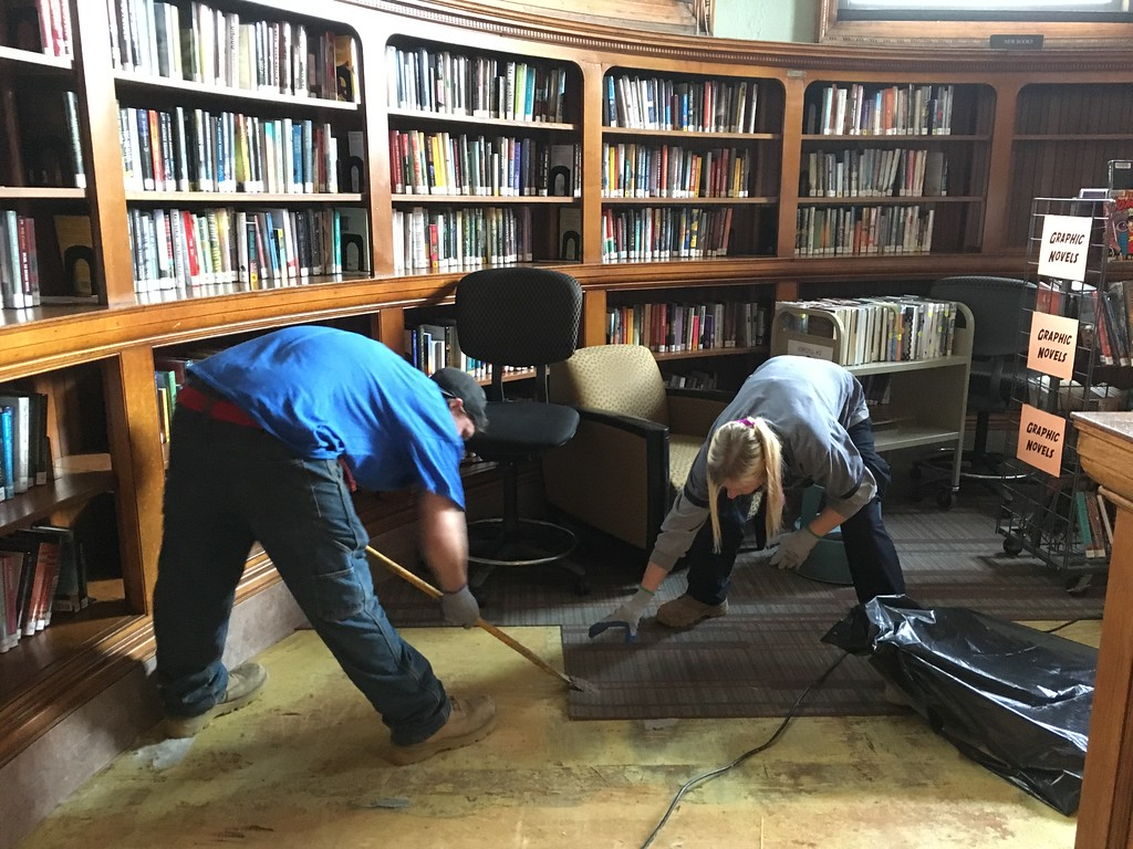 . ServiceMaster employees Jacob Scott, of Concord, N.H., and Jenn Clarke, of Nashua, remove damaged carpeting from the first floor of the Pollard Memorial Library Thursday.  SUN / ALANA MELANSON