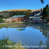 Scenic view over the garden pond towards the cottage and the Quantock Hiils.