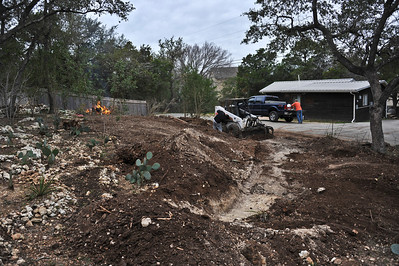 After removal of numerous cedar trees, the base of the retaining wall was excavated with the help of a neighbor's Bobcat.