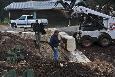 Here the blocks are put in place with the Bobcat and a French drain is constructed.