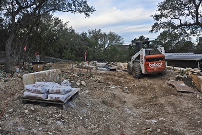 The liner is placed and large landscape boulders are moved into place around the pond.