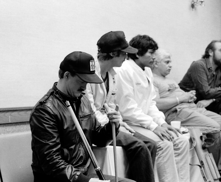 Robert Denham checking some cues he probably just bought. Efren Reyes (white jacket) and Warren Costanzo to the right.