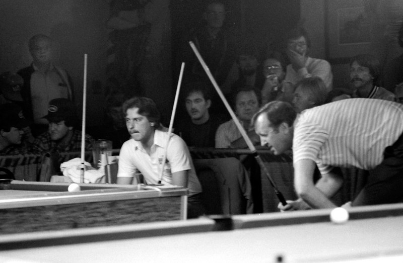 Earl Strickland sits as Dave Bollman lines up a shot. My old friend Ken Denham is the spectator right in the center of the shot, outlined by the two cue sticks. Sadly, Ken died a few months ago in a traffic accident. Jack Jarvis, a strong player from the Cincinnati area, is just to the right of Ken.
