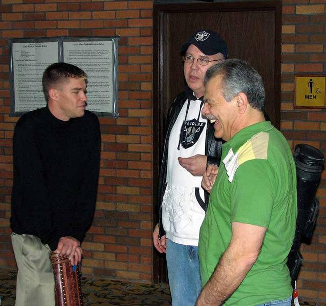 Corey Deuel leans on cue case as Bill Incardona laughs