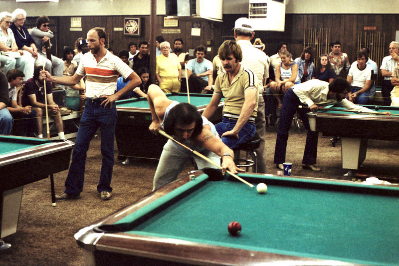 """Richie Ambrose shooting; Steve Smith standing; """"Country"""" Calvin behind Ambrose - aka """"Arkansas"""" Calvin. I am told that Calvin Harcrowe won the tournament in 1987 when it was held at Stroker's in Austin. Sharon Townsend commented that, """"the man in yellow leaning against the pole is John Lowry, an old-time road hustler, now deceased, who was married to Wilma Lowry, manager of Moyer's who, along with Joe Cromley, started the Texas Open."""""""