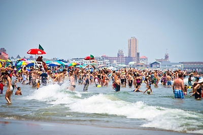 """""""Avon by the Sea Beach Scene""""  AVON, NEW JERSEY/USA – JULY 7: Big crowds of sunbathers seek relief from the week long heatwave enjoying the surf on July 7, 2012 at the beach in Avon NJ."""