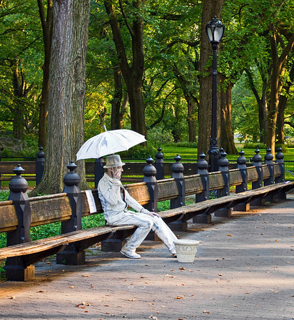 """Sitting Mime Central Park""  A man in Central Park performs a mime of a statue figure with umbrella seated on a park bench."