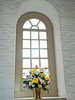 """Flowers in Window""  A vase of fresh cut flowers in an old church in Colonial Williamsburg, Virginia."