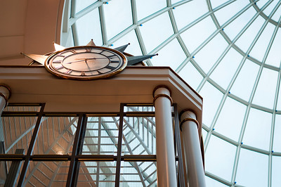 """Time""  A clock with Roman numerals and skylight roof in a modern shopping mall in New Jersey."