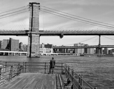 A timeless black and white image of the Brooklyn and Manhattan Bridges over the East River.