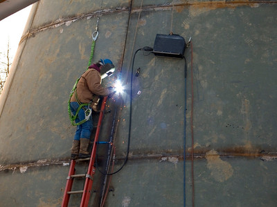A welder working on a water tank.