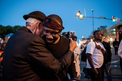 "Priest hugging a member of the ""Bloods"" gang in Baltimore, Maryland during the riots following the death of Freddie Grey at the hands of the Baltimore City Police Department."