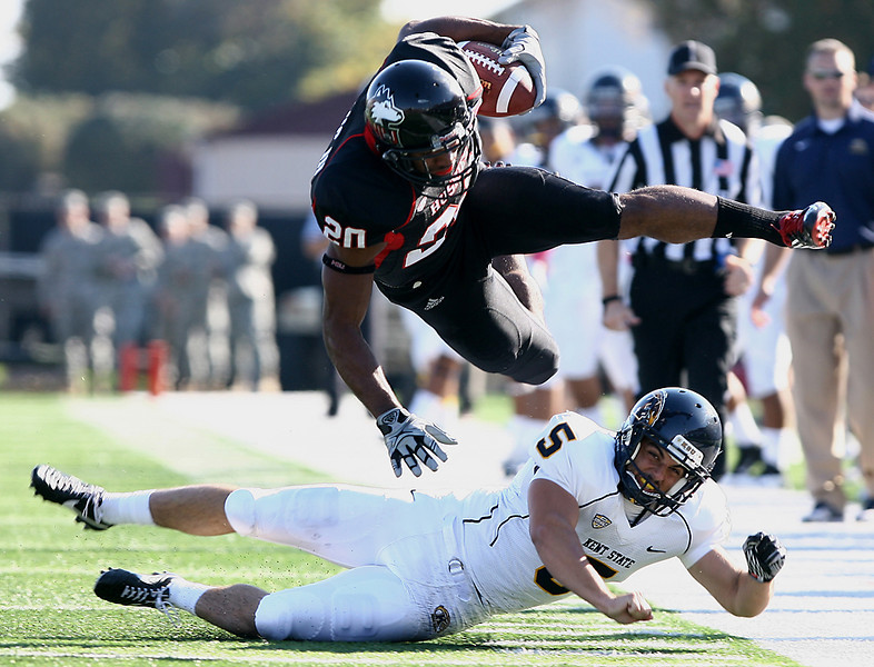 Erik Anderson | The Northern Star<br /> Northern Illinois University safety Tommy Davis jumps over Kent State punter Matt Rinehart Saturday, October 9, 2011 during the match up at Brigham Field in Huskie Stadium in DeKalb. THe Huskies would end up beating the Golden Flashes 40-10.