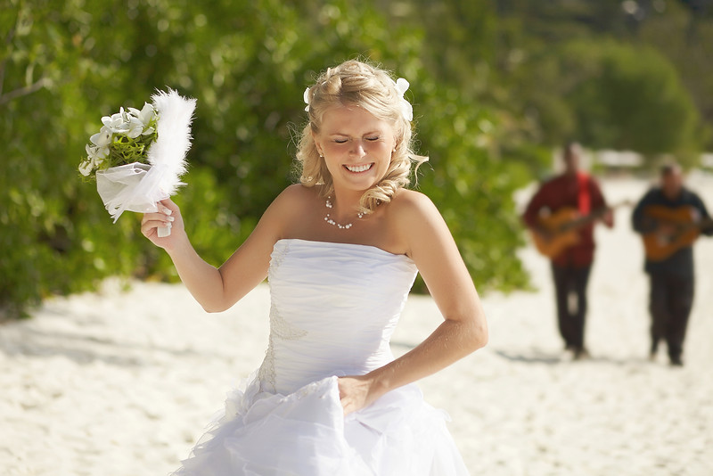 Gorgerous Bride Walking To Wedding Ceremony On The Beach With Bouquet