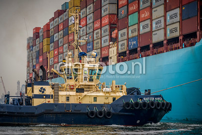 Tugboat pulling Containership from the quay in Port of Rotterdam
