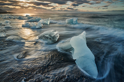 The captivating and surreal view of Diamond Beach in the early morning in Jokulsarlon, covered with large melting pieces of a glacier, with the gentle waves of the sea rolling in over them. South-East, Iceland