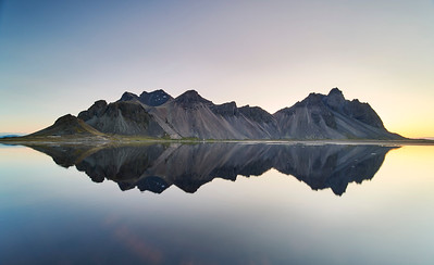The shimmering mirror image of Vestrahorn Mountain and Stokksnes beach, with a hint of sunrise. Stokksnes peninsula, Iceland. Early morning.