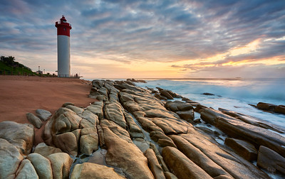An early morning picturesque stratocumulus sky of the iconic Umhlanga Rocks Lighthouse and waves rolling onto the rocks on the shore. Durban, KwaZulu-Natal Natal, South Africa