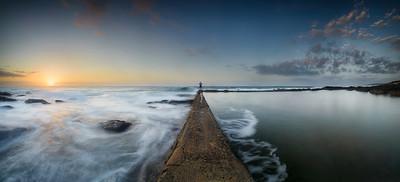 Fisherman at end of sea wall at dawn