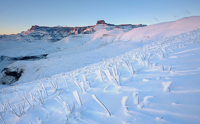 Snow and ice on a slope with the Drakensberg Amphitheatre in the background, Witsieshoek, Free State Province, South Africa