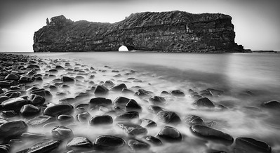 The Hole in the Wall at Coffee Bay is a unique structure with a huge detached cliff that has a giant opening carved through its centre by the waves. This black and white horizontal image of the unique opening was taken from the stony pebbled beach in the early morning.