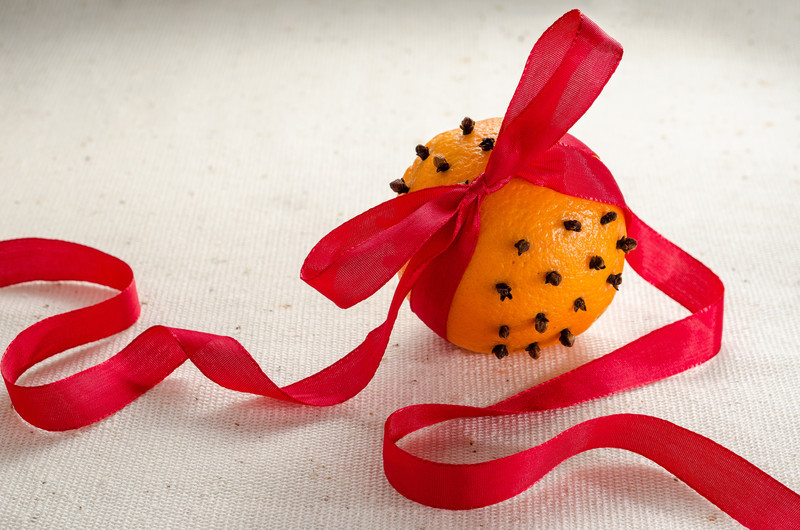 Orange decorated with cloves and ribbon