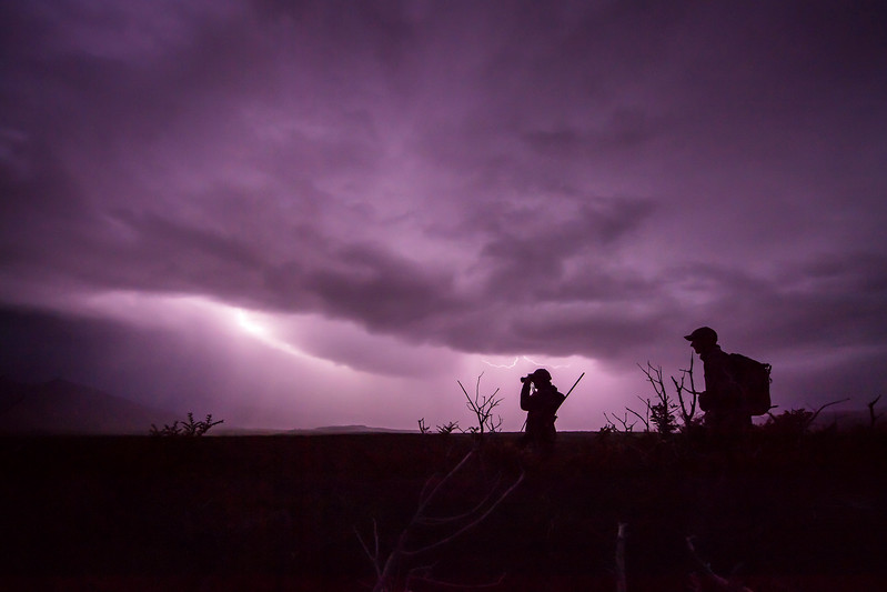 Big game hunters at dusk with dramatic lightening filled sky.