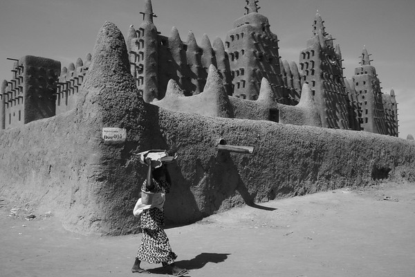 A woman walks past the Great Mosque of Djenne, Mali