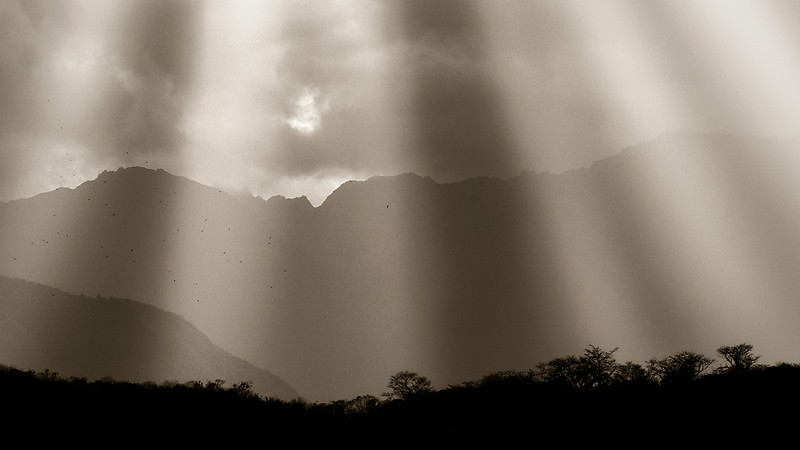 God Beams of light luminate the Andean mountain sky