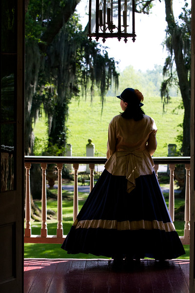 June 4, 2012 - Southern Belle of Houmas House, Darrow, Louisiana.<br /> <br /> Okay, she was our tour guide. During the mansion tour, she opened the upstairs double doors onto the front portico.  When she stepped to the rail as I had hoped she would.. she looked longingly (an act??) at the leveed Mississippi just across the river road outside the gates.  I quickly positioned myself mid-hallway and called to her to be real still and look to her left..  She obliged and this is what I saw..  I do not recall her name but I did promise her I'd give her an image...  I must contact the plantation and find her.  She was perfect for the part..  <br /> <br /> Houmas House - The Crown Jewel of Louisiana's River Road. <br /> <br /> Taken April 5, 2012.<br /> <br /> Thanks for remaining interested in our Louisiana Portfolio... we won't bore you much longer..<br /> <br /> HB
