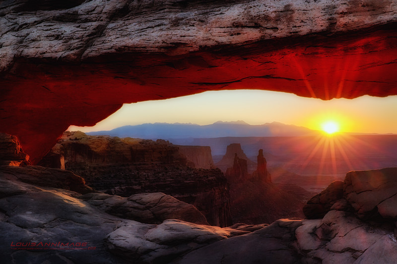 """The sun breaks at Mesa Arch, Version II - Where few tread...<br /> <br /> Our #1 'Bucket List' location... Yes, there's no shortage of images of this scene, here on SM or elsewhere.  Every image has a different feel, season or perspective - but all are spectacular.  But still, we needed our own view.  I've long dreamed of standing here to photograph what is likely the most familiar southwestern sunrise view ever published.  Red and I planned two mornings and two evenings in Moab, UT. to be sure we could visit Mesa Arch first in the daytime, to plan and scout our our sunrise return. Approximately a quarter-mile hike from the Islands in the Sky Mesa Arch trailhead in Canyonlands National Park, getting to the arch and staking claim to a decent tripod spot meant departing Moab at about 4:30 AM for a 7:00ish sunrise.  We had read that some mornings, 40+ tripods are fighting for a view - when in reality, only about 3 spots provide a perfect perspective.  We were early enough to claim one of those 3! So, for about an hour - with sunrise at the halfway point, we composed and bracket-shot about 450 images from which to work both single and HDR images.  Shifting from our 10-20MM to our 24-70MM we went about feverishly capturing the ever changing scene.  Funny thing though...  we'd like to return and do this again - without a camera... and just soak it all in. <br /> <br /> Viewed in 'Largest Size' you will see 'Washer Woman Arch.'  She's the left of two formations rising from the valley floor - just left of image-center. A rock appearing as a woman wearing a long dress working her wash - facing the sun..  The arch is more visable of course, if viewed from further south (right) looking back northward (left.)  <br /> <br /> See More of AZ and UT National Parks here:<br />  <a href=""""http://smu.gs/RfQCCf"""">http://smu.gs/RfQCCf</a><br /> <br /> Some ask why the bottom of the arch glows so..  As the sunlight illuminates the red earth of the cliff below the arch and then bounces upwa"""