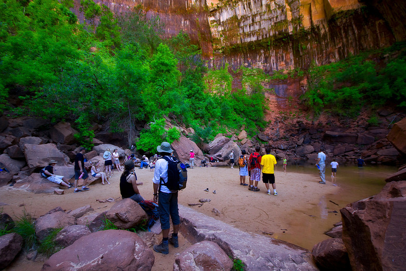 Hikers rest and enjoy the Upper Emerald Pool. Zion National Park, Utah.