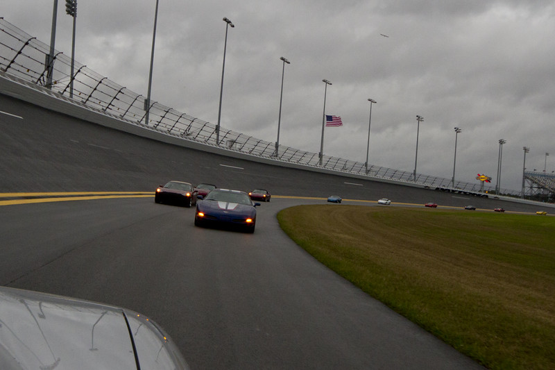 Red rolling into turn 4 off the super stretch.  The Rolex Series Opener Week - Captured on Friday Jan 27.  This is the Corvette Parade Lap. Rainy day..  Daytona International Speedway -