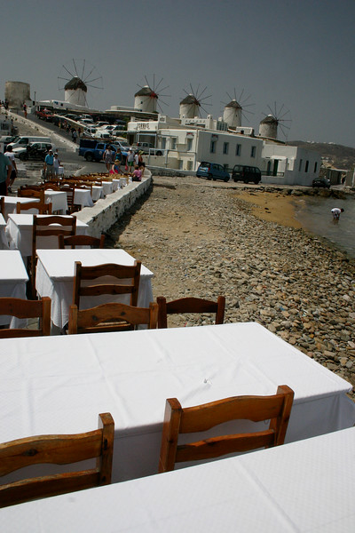 Mykonos at noon, a palate of color and contrasts. - This seaside village sports dozens of small churches with redish brown domes, a quaint harbour where tiny boats rest at anchor and pink pelicans roam the narrow alleyways.