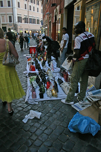A narrow alley leads to the Trevi, past street vendors, shops and cafe's.