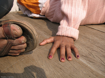 Man's foot, girl's hand, India