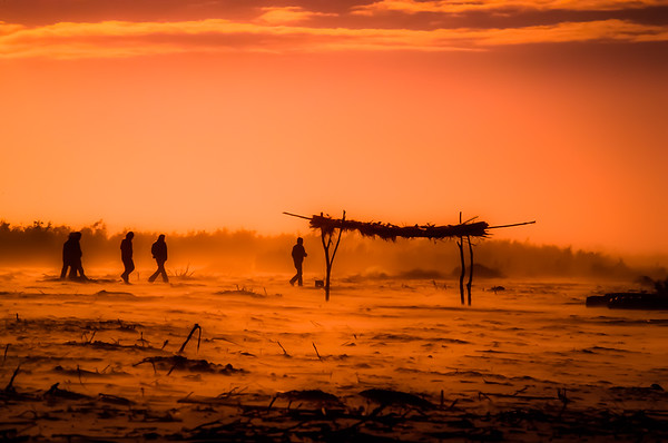 Farmworkers head back across the flats during a windstorm