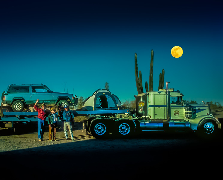 """It started with a trick my Dad taught me on our first trip to Baja… when the Pemex stations were out of gas, fill the old Scout with aviation fuel over at the airport. Fast forward to 1986, I was headed south down to Guerrero Negro with my buddy Grant to photograph the grey whales. A third of the way down the peninsula, we pulled into Pemex in Cataviña for fill up only to learn it would be """"mañana"""" before more gasoline would arrive! With only a quarter tank left, we had no choice but to kick in Dad's plan and head over to the small airport at Rancho Santa Inés for some high octane action! We pulled up to the traditional 55 gallon fuel drums at the airstrip's edge, assisted by Señor Zuñiga himself we filled the jeep with and hand pump, grabbed some machaca burritos for the road and continued south. Highway One winds it's way through the palm lined arroyos Baja California's Central Desert Natural Park. An hour down the road, we noticed that the Jeep was losing power as it climbed over the rocky landscape. I shifted down into second and we barely made the grade. Thinking we may have some water in the fuel line, I pulled over and tried some additive, but the engine barely held an idle… then died and would not restart. It was time for a tow truck… we were pulled into Guerrero Negro's Auto Repair Shop After dark. This wasn't my first breakdown in Baja, I've trusted the master mechanics in the most remote pueblos to make some amazing repairs!  But this time was different, they spent a long day fidgeting with my new Jeep and could not get it running! We we're left with no choice, we would have to tow it over 450 miles back to San Diego. Plan A was a tow truck, but that seemed like a crazy distance…  Plan B maybe a tow bar behind another vehicle? It was at that moment when Plan C appeared, an 18 wheeler with a flat bed headed down main street of the small pueblo.  We explained our situation to the driver… after some pricing discussion, we loaded the Jeep on back of the flatb"""